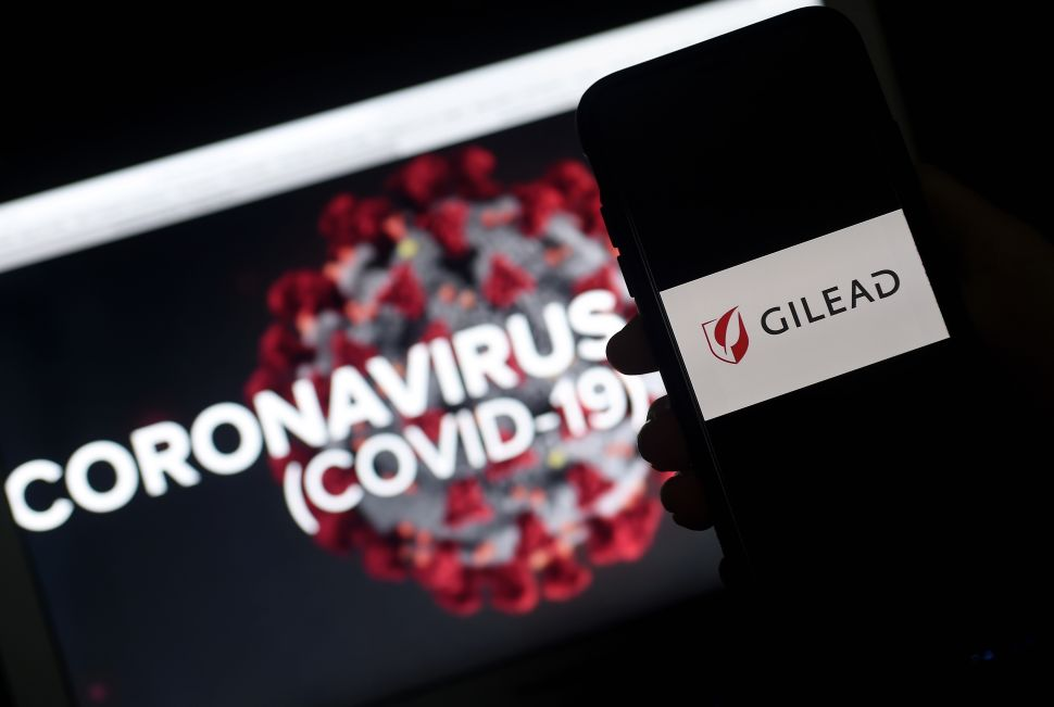 In this photo illustration a Gilead logo is displayed on a smartphone next to a screen showing a coronavirus graphic on March 25, 2020 in Arlington, Virginia. - Gilead announced on March 25, 2020 that it has submitted a request to the Food and Drug Administration to rescind the exclusive marketing rights it had secured for remdesivir, an antiviral drug that shows promise in treating Covid-19, the disease caused by the new coronavirus. (Photo by Olivier DOULIERY / AFP) (Photo by OLIVIER DOULIERY/AFP via Getty Images) | nigerian doctor babafemi taiwo